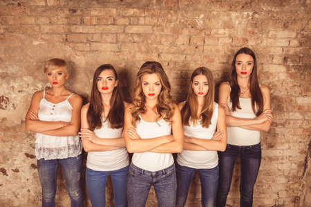 dress code: Confident serious young women with red lips wearing dress code Stock Photo