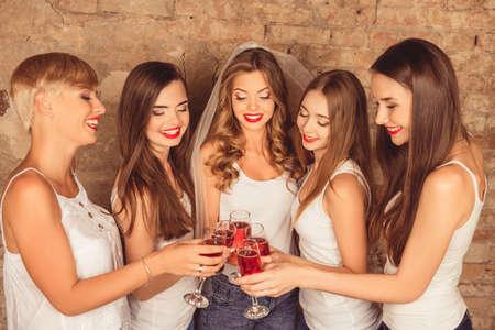 Leuke bruid en gelukkige bruidsmeisjes vieren kip-partij met rode champagne