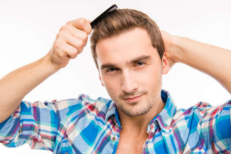 cheeky: Handsome cheeky young man combing his hair Stock Photo