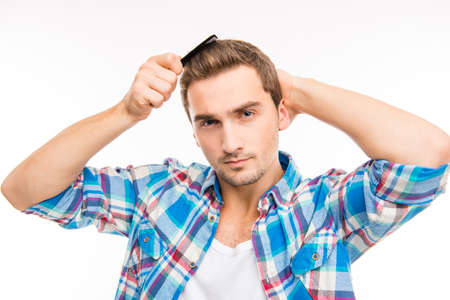 comb hair: Handsome confident young man combing his hair