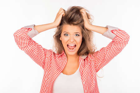 crazy hair: Portrait of crazy young woman shouting and holding hair Stock Photo