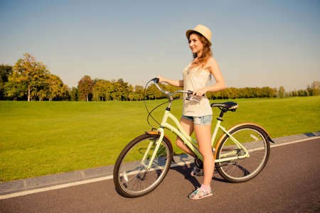Sexy Shapely Girl With Hat And Mini Shorts Ride A Bicycle Stock