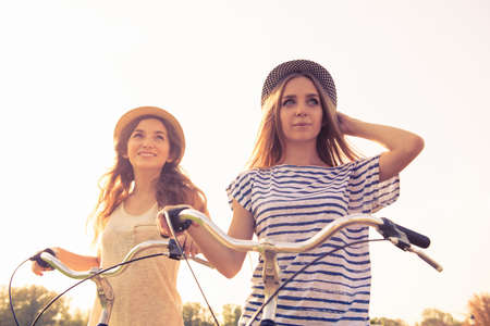 lesbian sexy: cherful  happy girls with hat ride bicycles on the park