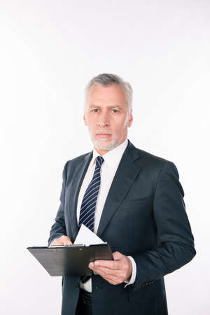 businessman pondering documents: Old confident businessman holding a folder with documents