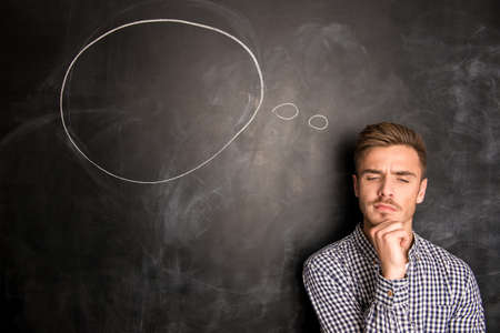 viso di uomo: Il giovane sullo sfondo di lavagna pensare al problema Archivio Fotografico