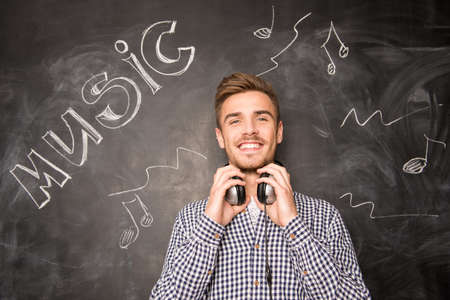 stubble: Young happy man with headphones against the background of chalkboard Stock Photo