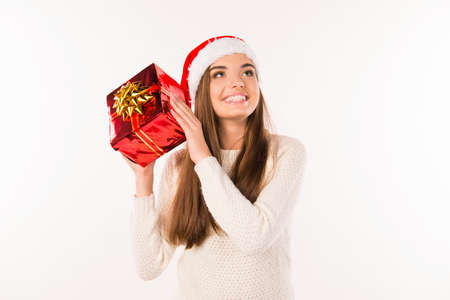happy surprised girl in santa hat with christmas presents
