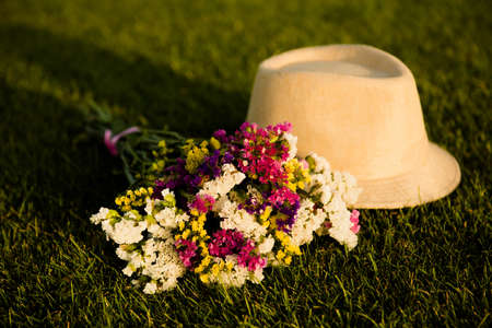 girlish: cream girlish hat and the bouquet on the green grass