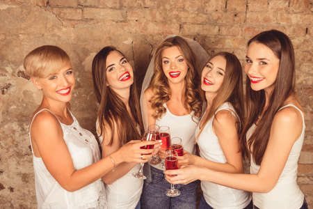 bachelor: Cute young women wearing dress code celebrating hen-party with sparkling wine