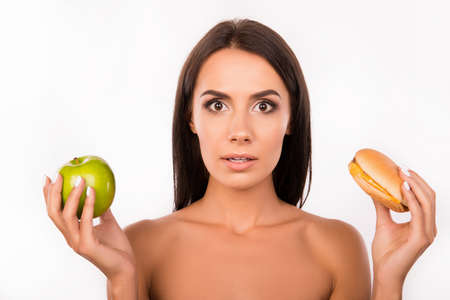 decided: hard choice: apple or burger, flustered girl decided to go on a diet