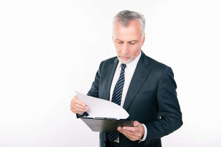 businessman pondering documents: Old confident businessman reading information in a folder