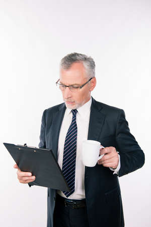 businessman pondering documents: Aged confident businessman with glasses reading information in a folder holding a cup
