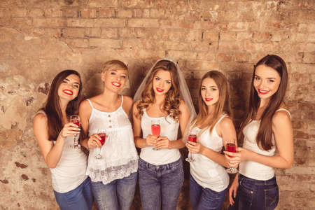 bridesmaids: Beautiful bride and happy bridesmaids celebrating hen-party with red champagne Stock Photo