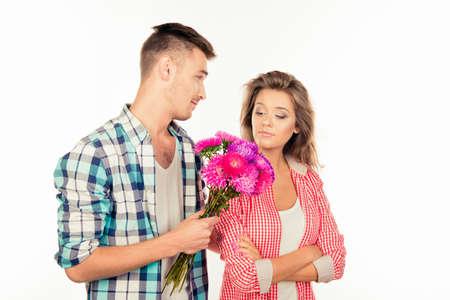 잘 생긴 젊은 남자가 그의 귀여운 사랑에 꽃다발을주고 그를 용서해달라고 스톡 콘텐츠