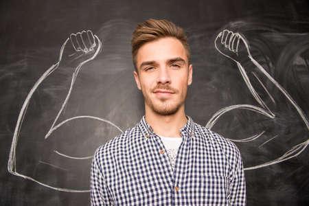 muscle: Joven contra el fondo de los músculos representados en la pizarra