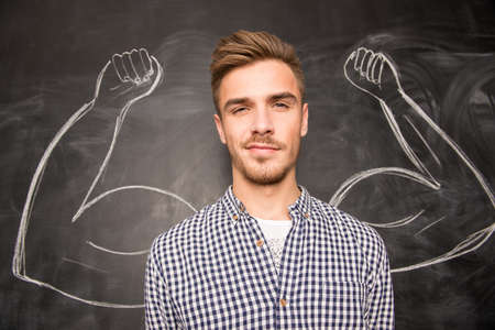 muscle people: Young  man against the background of depicted muscles on chalkboard