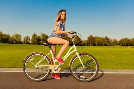 sexy shapely girl with hat and mini shorts ride a bicycle