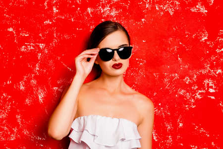 pomatum: Fashionable girl holding the glasses against the red background