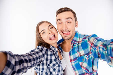 love story: Cheerful funny couple in love making selfie photo showing tongue Stock Photo