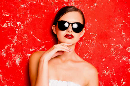 pomatum: Glamorous girl with cool  spectacles posturing against the red background