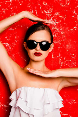 pomatum: Glamorous girl with cool  spectacles posing against the red background