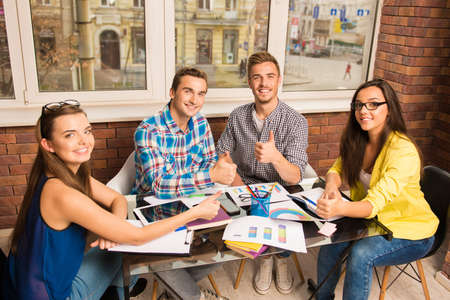 freelancers: Perspective successful freelancers working with a business project gesturing thumbs up Stock Photo