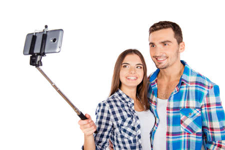 Cheerful couple in love making selfie photo with selfie stick Stock Photo