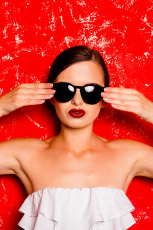 pomatum: Glamorous cheerful girl with cool  spectacles against the red background