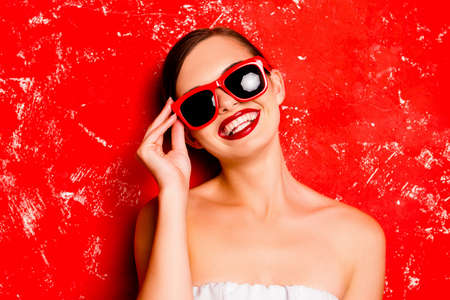 Glamorous girl holding the spectacles against the red background Stock Photo