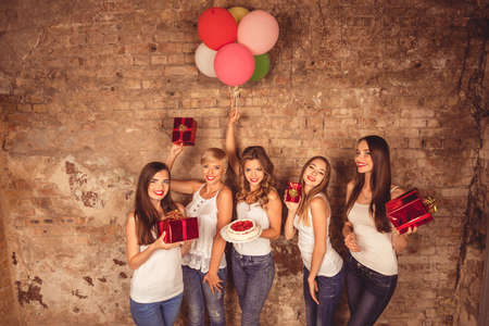 hen party: Happy nice-looking girls holding birthday cake, balloons and presents