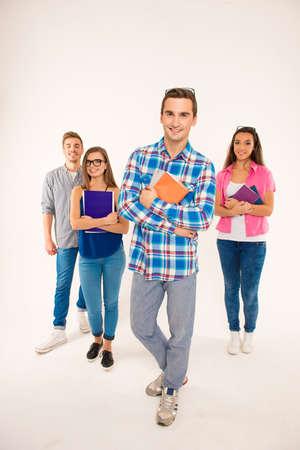 Gelukkige groep studenten die boeken en materialen houden die rechtstreeks lopen