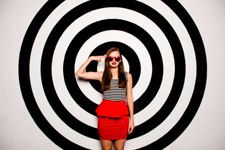 basque woman: Glamorous girl with glasses in a red skirt-basque against the background of circles gesturing Stock Photo
