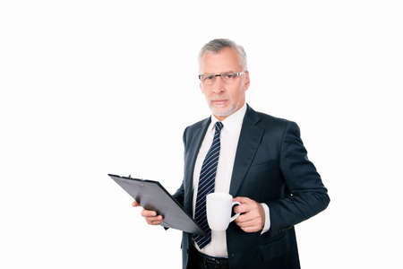 businessman pondering documents: old confident businessman with glasses holding a folder and a cup Stock Photo