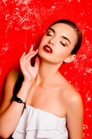 pomatum: Cute girl touching her face against the red background