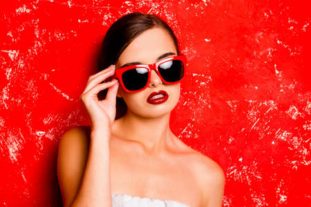 pomatum: Glamorous cute girl with red lips holding the spectacles against the red background