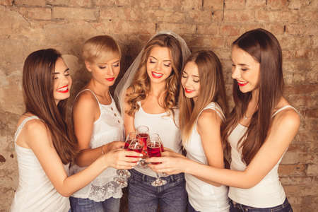 hen party: Happy young women wearing dress code celebrating hen-party with sparkling wine