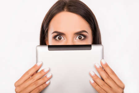 woman hiding: Frightened young woman hiding face behind the tablet Stock Photo