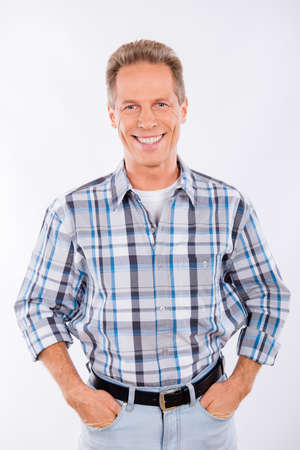 male fashion: Handsome happy aged man keeping hands in pockets Stock Photo