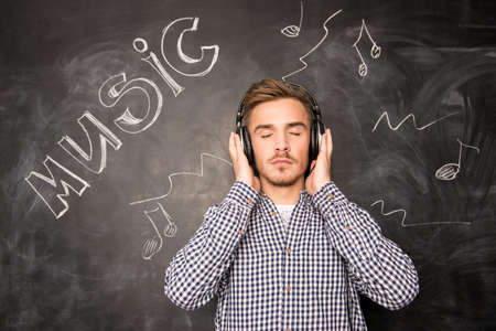 listens: A young man listens to music in headphones