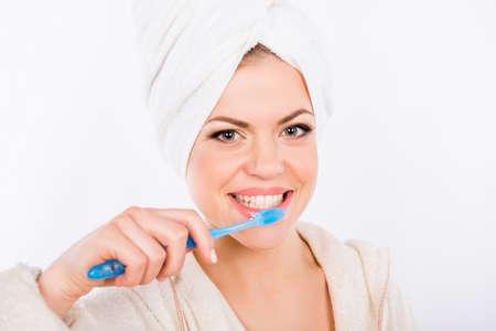 diente: La muchacha bonita se cepilla los dientes sobre un fondo blanco