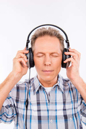 shutting: Aged calm hipster with headphones listening to music