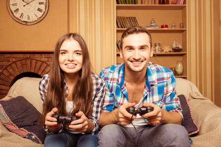 home entertainment: couple playing video games on the couch. concept about home entertainment