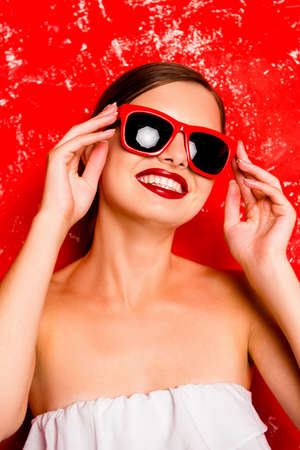 pomatum: Glamorous cheerful girl with red lips with spectacles against the red background