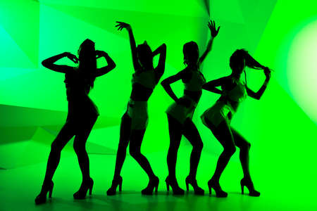 tempter: Black silhouettes of dancing girls on green background Stock Photo
