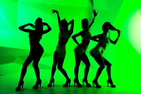 gogo girl: Schwarze Silhouetten von tanzenden Mädchen auf grünem Hintergrund Lizenzfreie Bilder