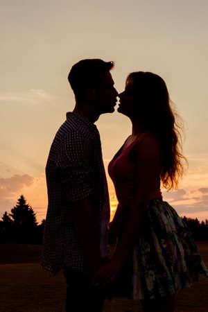 siluetas de enamorados: fecha de la puesta del sol Foto de archivo