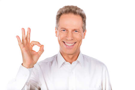 Confident man gestures OK  suggesting acceptance, approval