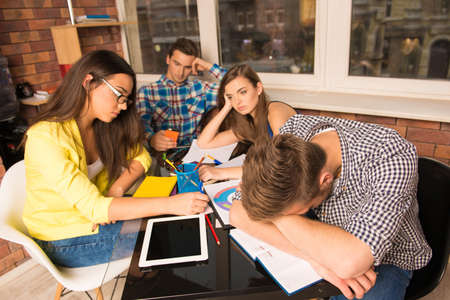 一緒に頑張って疲れている学生のグループ