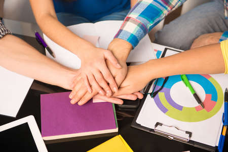 businessplan: United group keeping hands on each hand working on business task
