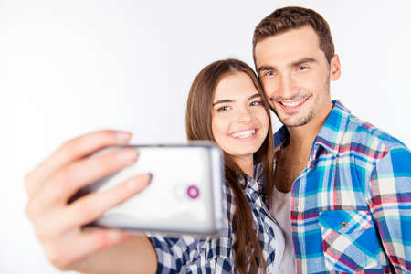 making fun: Closeup photo of a cheerful pretty couple in love making selfie